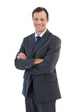Charismatic smiling businessman standing with arms crossed Stock Photography