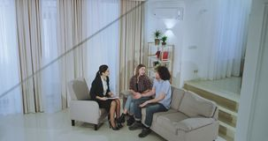 Charismatic and smiling couple have a appointment with their real estate agent in a modern spacious house they chatting. About the contract to buy a house at stock video footage