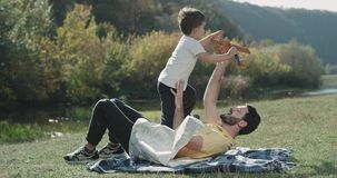 Charismatic three years old boy playing funny with his dad with a airplane at nature, they laying down on the grass. stock footage