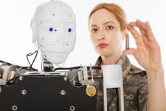 Charismatic trained officer working on secret military project. Teaching the machine. Young serious progressive woman developing new weapon in the lab while stock image