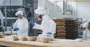Charismatic very enthusiastic young baker dancing and working in a big bakery industry while forming the dough. Background workers moving the shelves with bread stock footage