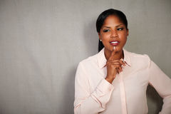 Charismatic woman thinking with hand on chin Royalty Free Stock Photo