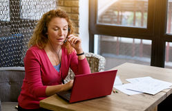 Charismatic woman using modern devices in the cafe Royalty Free Stock Photos