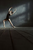 Charismatic young ballet dancer training in the black colored room Stock Image