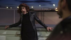 Charismatic guy dressed like woman, wearing black clothes and wig, sings outside stock video footage