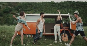 Charismatic young group of friends dancing at the nature , in the middle of field , behind a retro van. 4k