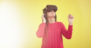 Charismatic young lady multi ethnic african and european using a VR to play in a yellow background studio closeup video. Taking , long african lady with stock footage