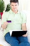 Charismatic young man with card and laptop on sofa Stock Photos