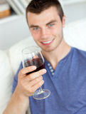 Charismatic young man holding a glass of wine Royalty Free Stock Images