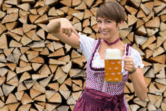 Charismatic young woman in a dirndl. Charismatic attractive young Bavarian woman in a dirndl pointing to a tankard of frothy draft beer with a happy smile royalty free stock photo