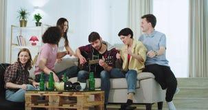 Charismatisch bedrijf van vrienden het multi etnische dacing en het zingen op een gitaar in de woonkamer brengen zij een goede ti stock footage