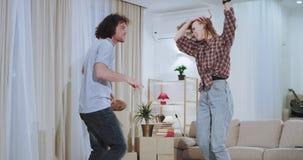 Charismatisch en grappig paar na een harde bewegende dag in een nieuw huis zij die en gelukkig in een nieuwe flat dacing voelen stock videobeelden