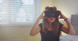 Charismatisch tienermeisje die een virtuele werkelijkheidsglazen op haar bed dragen, zij die een nieuwe technologie van virtueel  stock footage