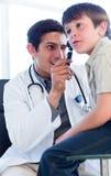 Charismatische arts die de oren van weinig jongen onderzoekt Royalty-vrije Stock Afbeelding