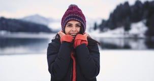 Charismatische jonge dame met een bruin ogenportret die recht en opgedirkt aan de camera haar rode hoed in het midden van kijken stock videobeelden