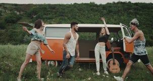 Charismatische jonge groep vrienden die bij de aard, in het midden van gebied, achter een retro bestelwagen dansen 4K stock video