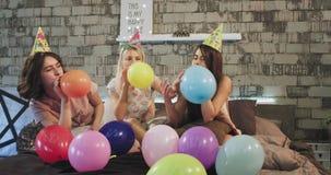 Charismatische jonge tienermeisjes die kleurrijke ballons voor de camera op bed dragen blazen pyjama's stock footage