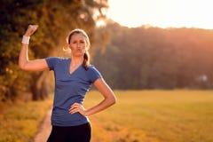 Charismatische junge Frau, die ihren Arm pumpt Lizenzfreie Stockbilder