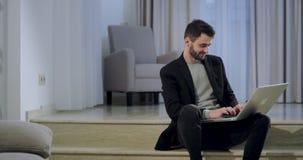 Charismatische knappe jonge mens die van notitieboekje werken terwijl thuis het zitten, concentreerde hij het typen en het voelen stock footage