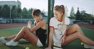 Charismatische Tennisspieler, die Frauen zum Beginnen sich vorbereiten, das Tennis am Tennisplatz, Trinkwasser spielend, sie, sin stock video footage