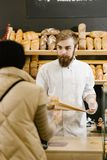 Charismatischer B?cker mit einem Bart und einem Schnurrbart gibt dem Kunden in der B?ckerei eine Papiert?te Brot lizenzfreies stockfoto