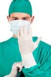 Charismatischer Chirurg, der chirurgische Handschuhe trägt Stockfotografie