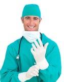 Charismatischer Chirurg, der chirurgische Handschuhe trägt Lizenzfreies Stockfoto