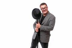 Charismatischer gutaussehender Mann im Anzug mit schwarzem dem possing Hut und Mikrofon Lizenzfreie Stockbilder