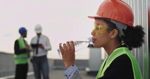 Charismatischer Ingenieur African der jungen Frau ethnisch, etwas Wasser auf der Dachspitze der Baustelle trinkend sie tragendes  stock video