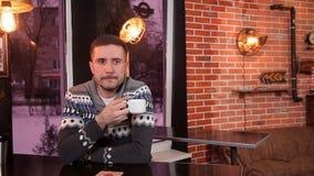 Charismatischer junger Mann trinkt Kaffee und benutzt einen Smartphone in einem Restaurant stock footage