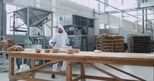 Charismatischer Mannbäcker mit dem Barttanzen lustig an seinem Arbeitstisch bei der Zubereitung des Teigs für backendes Brot in e stock video footage