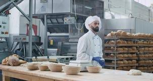 Charismatisches Mannbäckertanzen lustig während hörende Musik unter Verwendung der drahtlosen Kopfhörer in einer großen Bäckereik stock footage