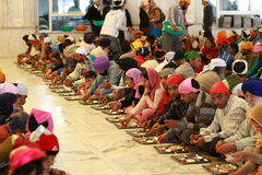 Charity. A group of poor people eating at a sikh temple in Delhi Royalty Free Stock Photography