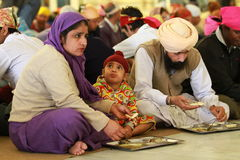 Charity. A family eating at a sikh temple in Delhi Stock Photo