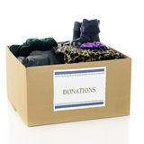 Charity Clothing Box. A large corrugated box with a Donations sign and filled with an assortment of warm, winter clothing.  On a white background Royalty Free Stock Photography