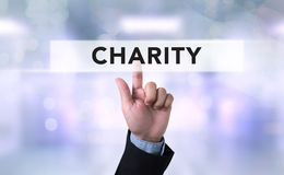 CHARITY DONATE Give Concept. Business man with hand pressing a button on blurred abstract background Royalty Free Stock Photo