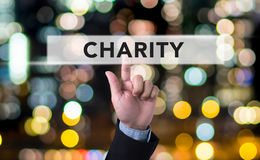 CHARITY DONATE Give Concept. Business man with hand pressing a button on blurred abstract background Stock Photography