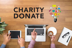 CHARITY DONATE Give Concept. Two Businessman working at office desk and using a digital touch screen tablet and use computer objects on the right Royalty Free Stock Photos