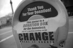 Charity donations. Close-up of a parking meter collecting donations for a homeless charity Royalty Free Stock Images
