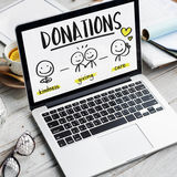Charity Donations Fundraising Nonprofit Volunteer Concept. Computer screen donations with notebook background Royalty Free Stock Photo