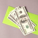 charity Envelope verde com dinheiro no fundo cinzento foto de stock