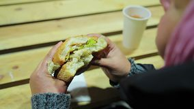 Charity event. Shelter for homeless. Hungry woman eating burger and drinking tea. Stock footage stock footage