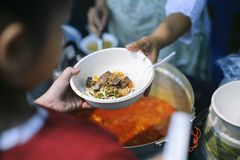 Charity food is the hope of the poor who have no money : concept of begging food : Donate food to people in society : Volunteers. Share Food to the Poor stock photography