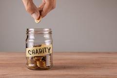 charity Frasco de vidro com moedas e uma caridade da inscrição O homem guarda a moeda foto de stock royalty free