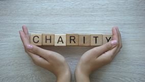 Charity, hands pushing word on wooden cubes, donations and helping in need
