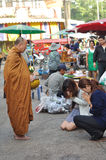 Charity lady. Two lady giving a food to the monk in Ton Lum Yai market, Chiangmai, Thailand Stock Photo