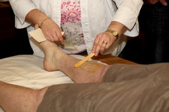 Charity leg waxing. Man getting his hairy legs waxed for charity Royalty Free Stock Image