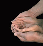 Charity. Male and female hands in gentle embrace on black background Stock Photo
