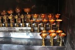 charity Rezando velas em um monastério em Butão imagens de stock royalty free