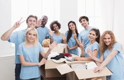 Young volunteers group working with clothing donation. Charity. Volunteers office, group of people sorting clothing donations, copy space royalty free stock photos
